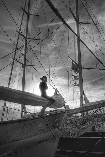 person sitting on ship rigging