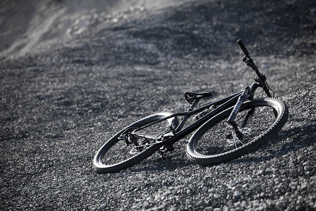 Black and white photo of bike laying on its side on arid hill