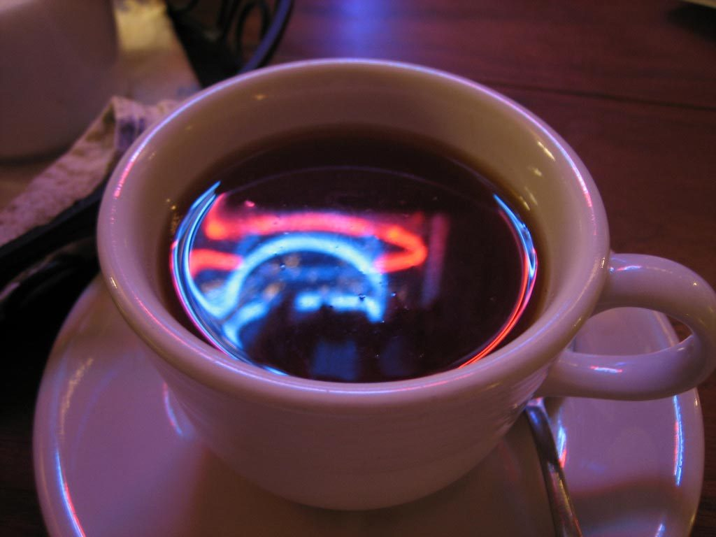 Neon lights reflected in teacup