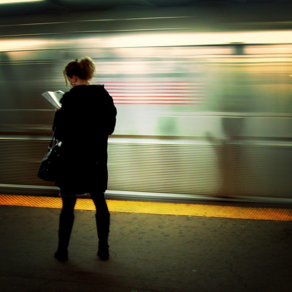 Woman reading in front of moving subway train