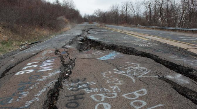 cracks in road with grafiti leading to Centralia, PA