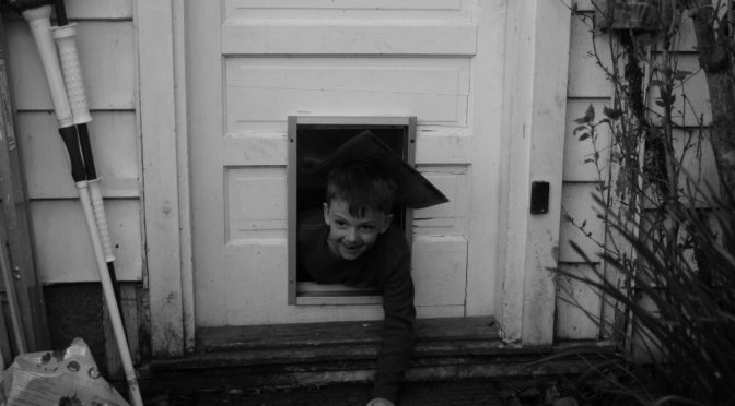 Boy crawling out doggie door