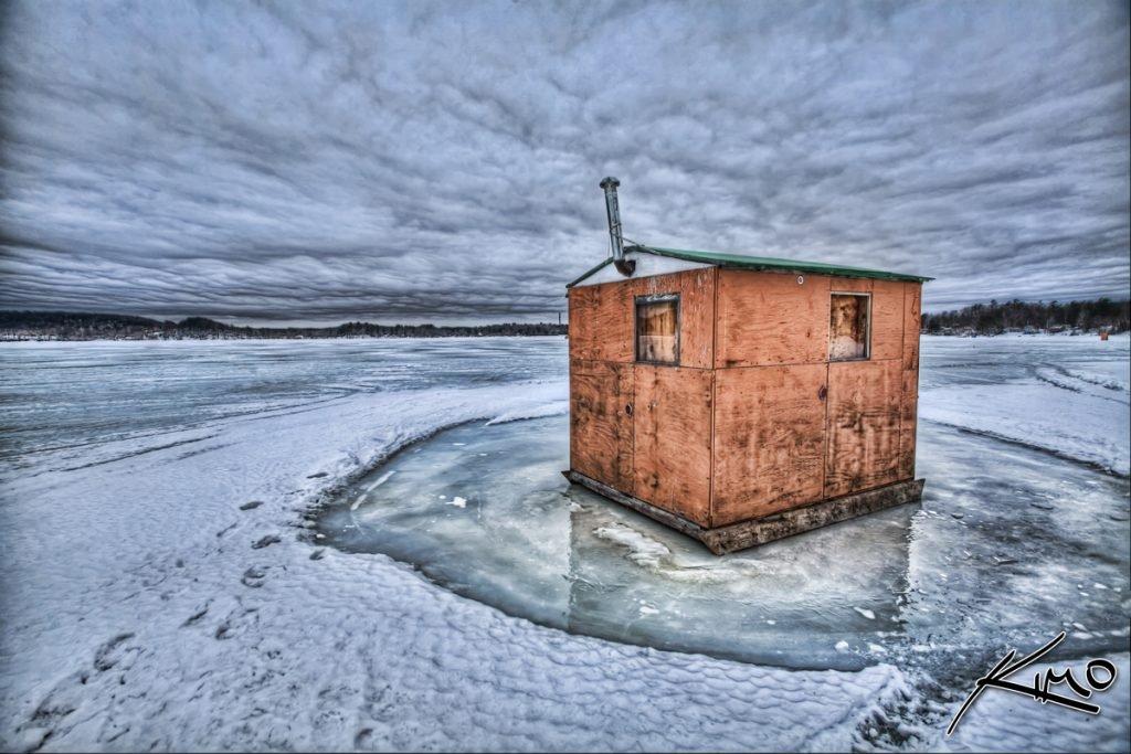 Ice fishing shack on frozen lake
