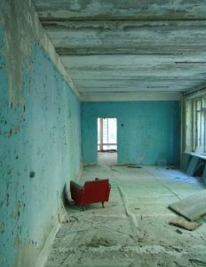 Crumbling empty room with red chair