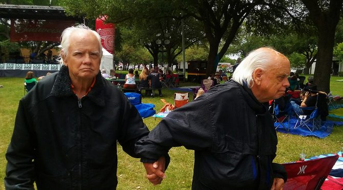 Two elderly male twins holding hands