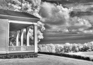 House under clouds in black and white