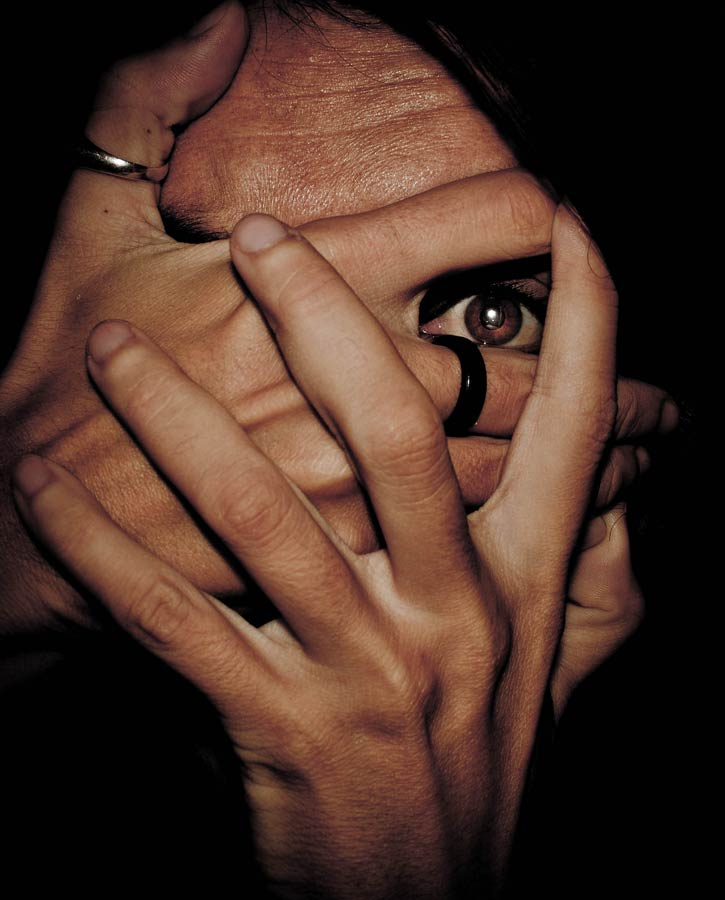 Eye peeking through hands covering face