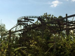 abandoned roller coaster overgrown by foliage