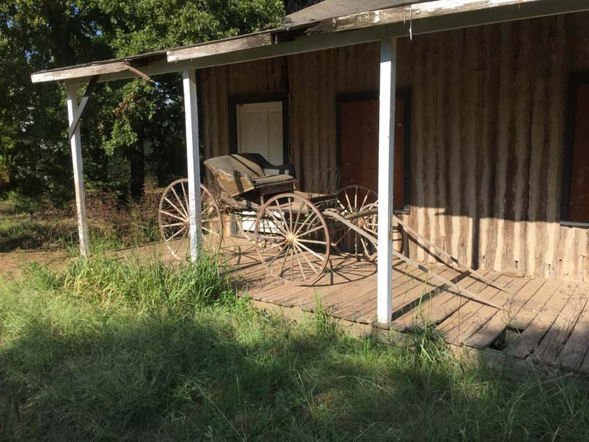 empty horse carriage on wooden porch
