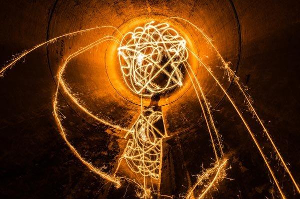 swirl of orange sparkler light in a dark tunnel
