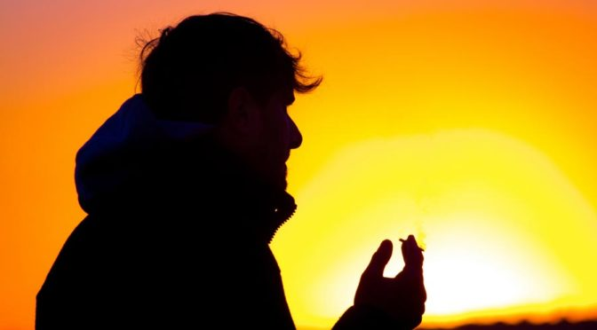 man smoking cigarette silhouetted against sunset