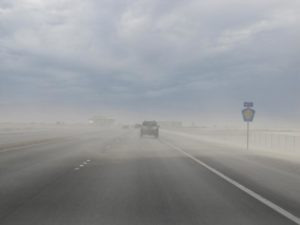 Dust blowing across road and darkening the sky