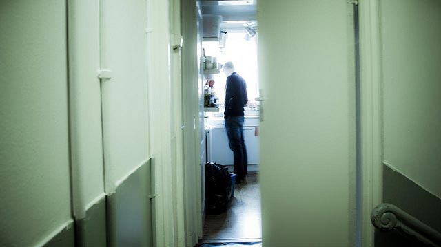 Man standing alone in kitchen off of forlorn hallway