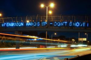lighted display of Ferguson solidarity message on highway overpass