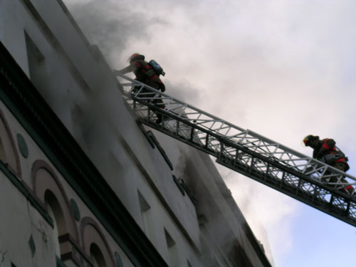 Black and white photo of firemen on climbing ladder towards roof