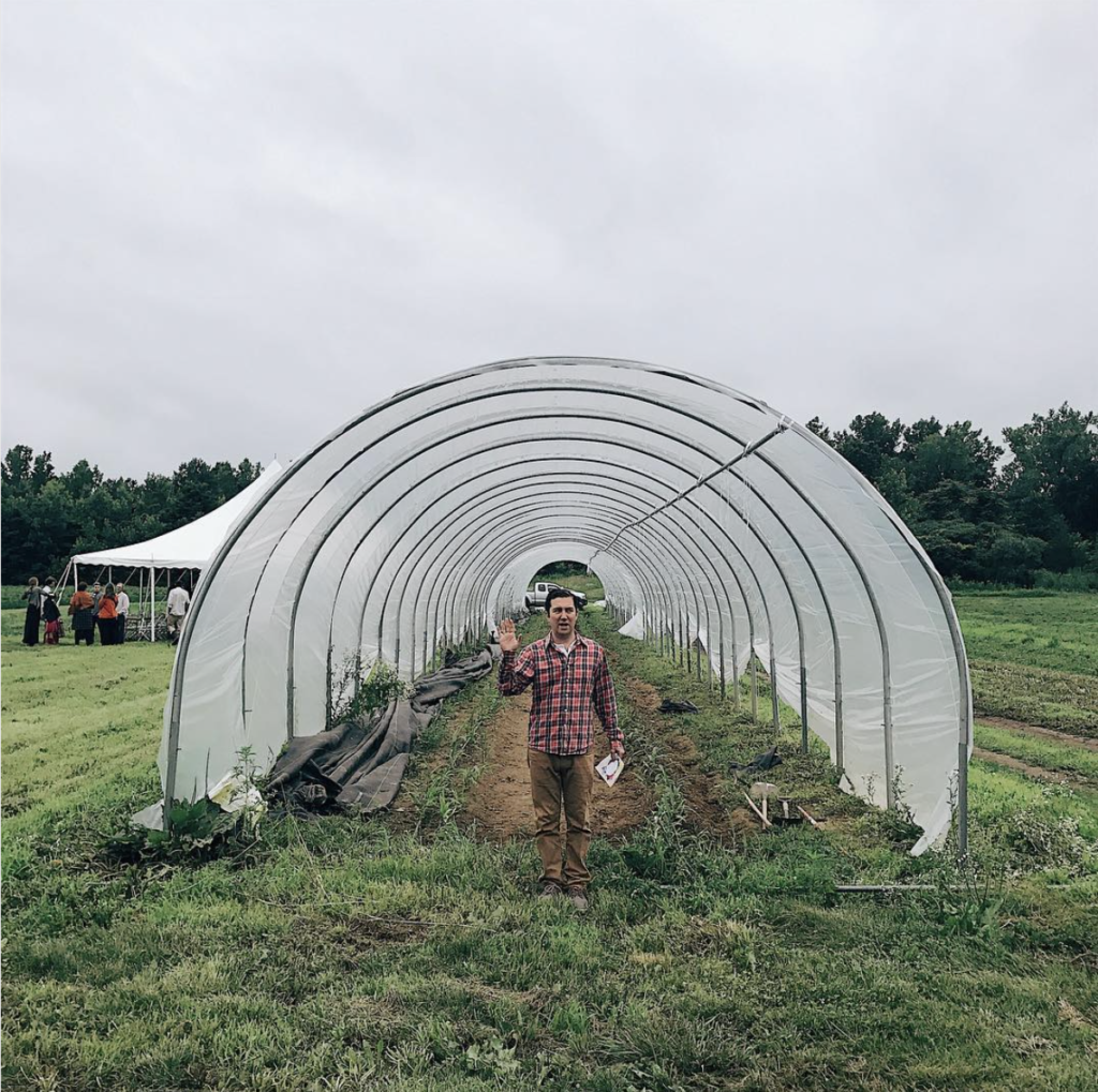 Man standing in front of greenhouse