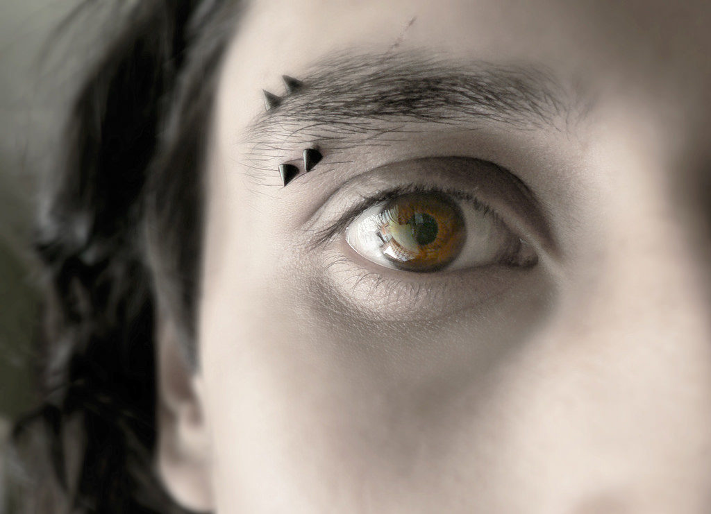 part of a face showing eyebrow piercings