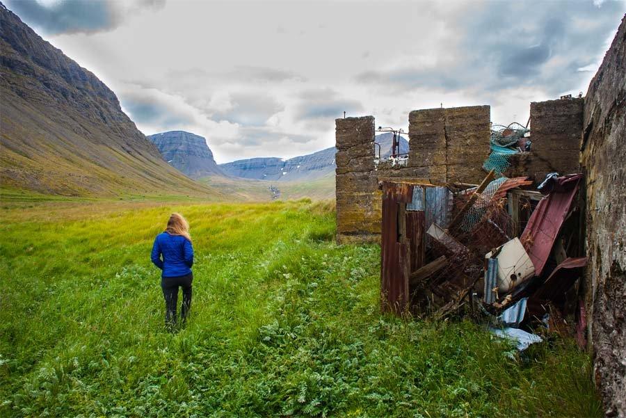 Woman walking in field next to stonework