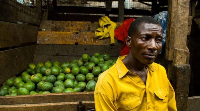 man in yellow shirt selling limes
