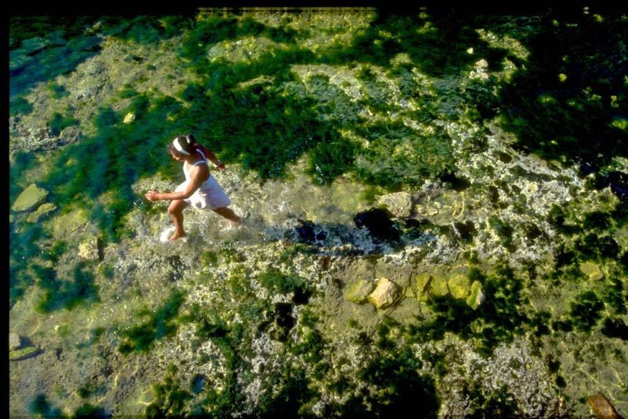 young girl waking through tidal pool