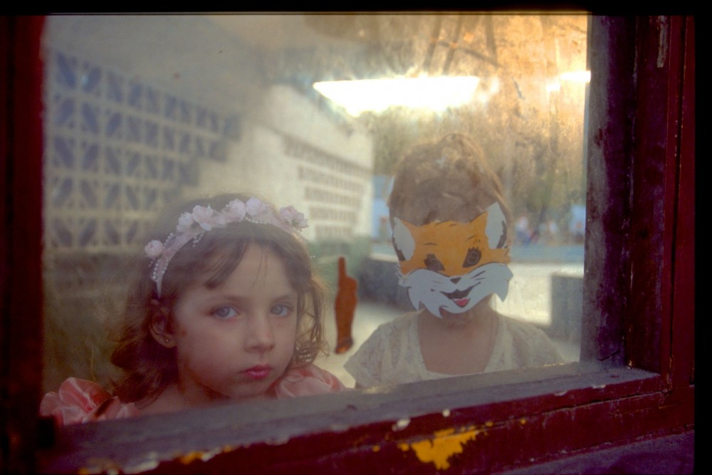 two young girls looking through window