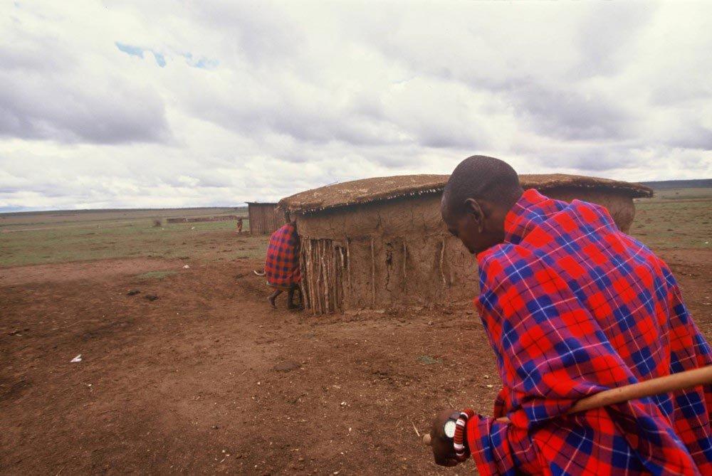 man on plains with cob hut