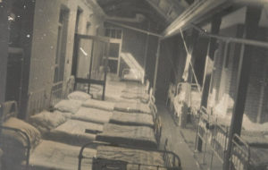 Black and white photo of old hospital ward full of empty beds