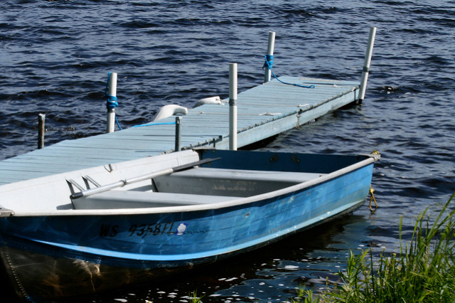 Empty blue rowboat next to dock