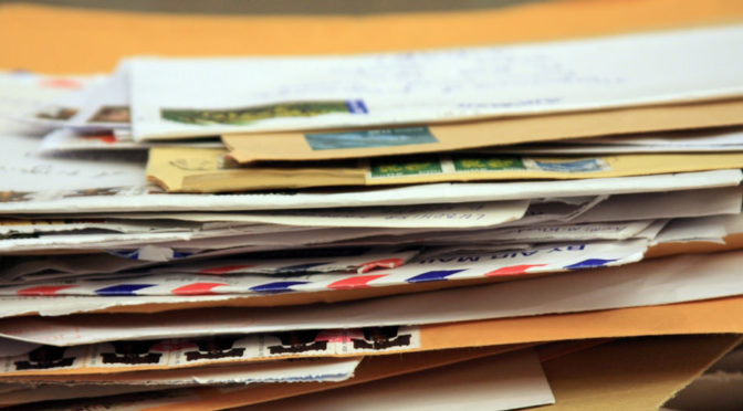 a pile of mail in envelopes