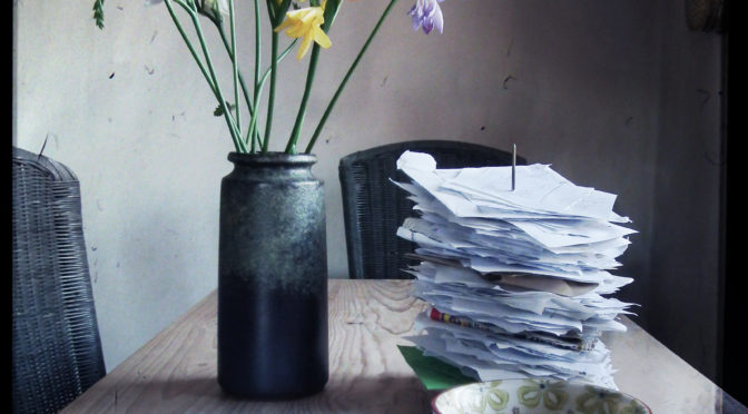Mug, vase of flowers and papers on table