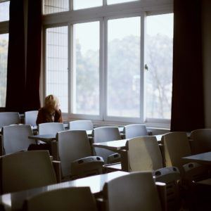 lone woman in room of desks