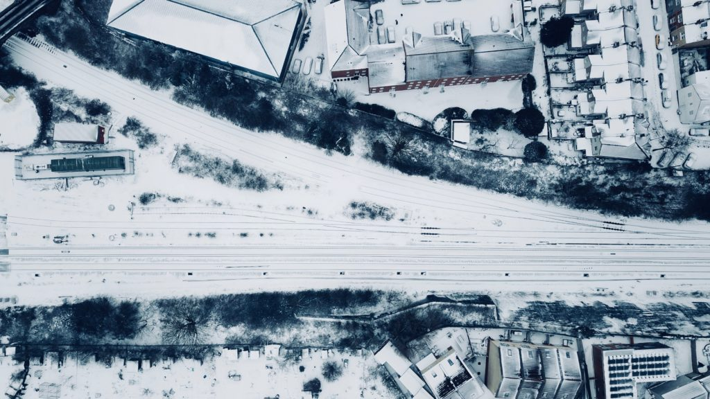 Aerial view of road and buildings coated with snow