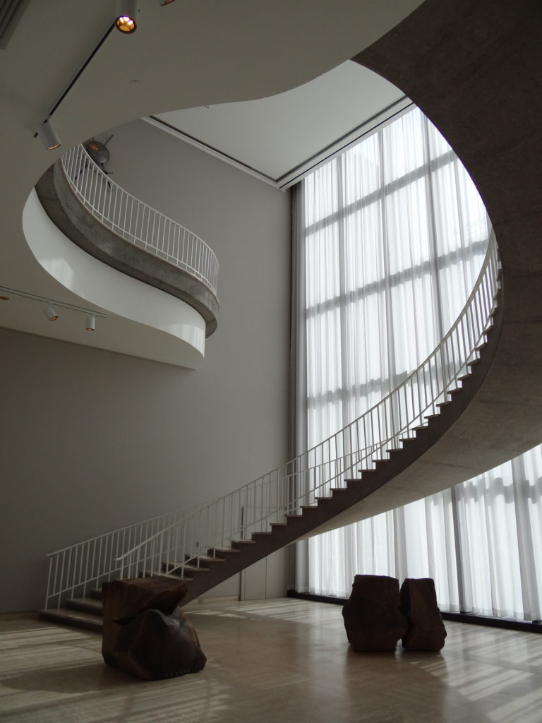 Giant, open, winding staircase by huge windows