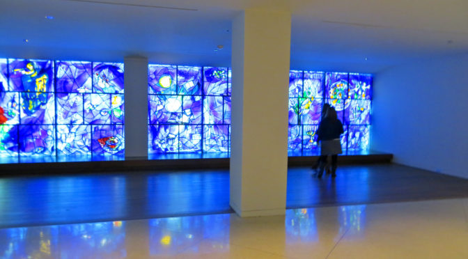 People standing before wall full of stained glass