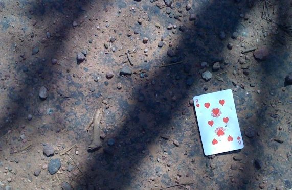 photo of a card-8 of hearts on sidewalk