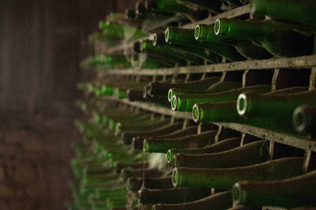 old green bottles in old wall wine rack