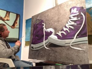 Loprete in front of canvas with purple shoes painted on it