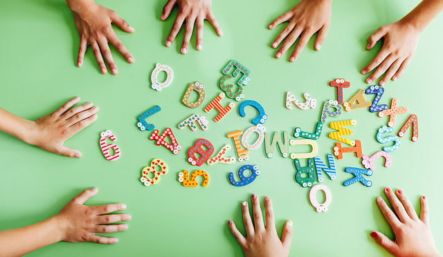 Alphabet letters on table with children's hands
