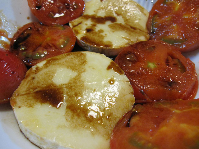 Camembert surrounded by sliced tomatoes