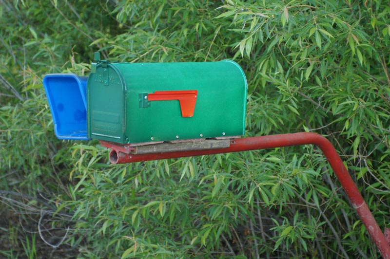 Green mailbox on red post