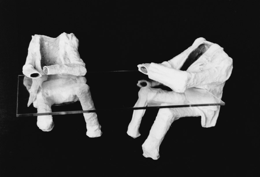 two plaster suit and pant sets supporting glass table top