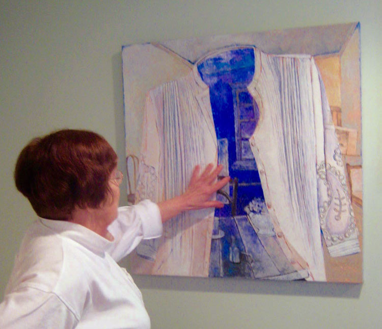 Joan Söderlund looking at her artowork in a gallery