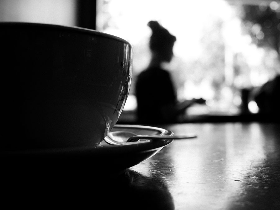 Coffee cup with woman in background, black and white