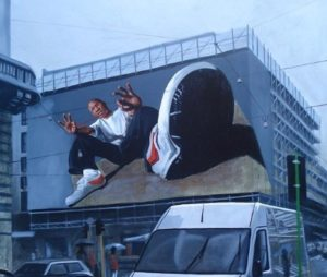 Billboard with painting of B-boy on side of building