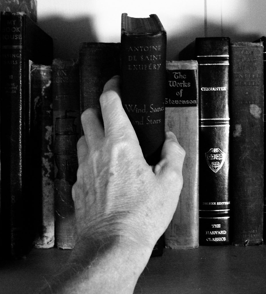 Black and white photo of books on a shelf with someone's hand reaching for a book