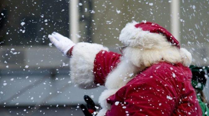 Santa waving in the falling snow