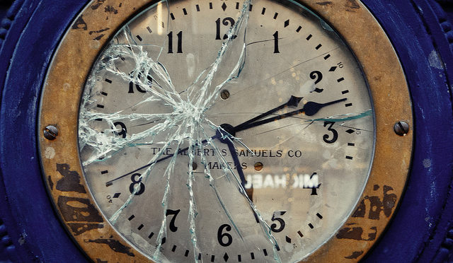 Photo of a clock with broken glass on face . Time: 5:12.