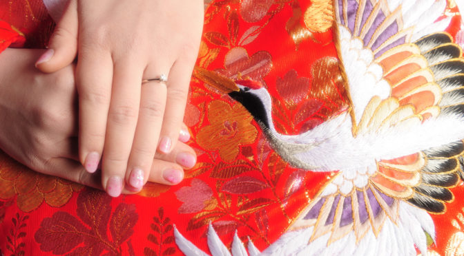 Photo of Japanese woman with crossed hands, engagement ring and red kimono