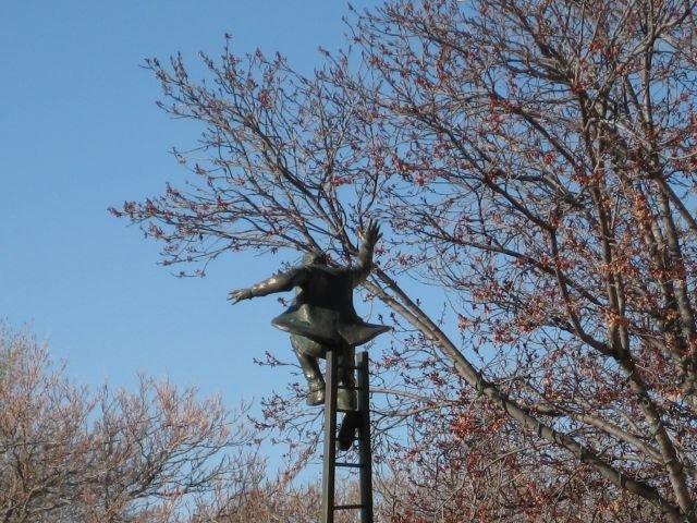 Statue at man at top of ladder