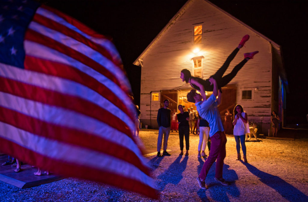 Man lifting girl over his head in front of barn, foreground of american flag
